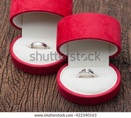 Diamond ring in red velvet box on wood - stock photo
