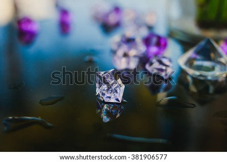 Diamond (small purple jewel) stones heap over mirror glass table, crystal stones, shiny gold and silver jewelery on a table - stock photo