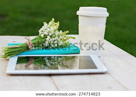 diary, a tablet computer, a glass of coffee and  lilies of valley on the table - stock photo