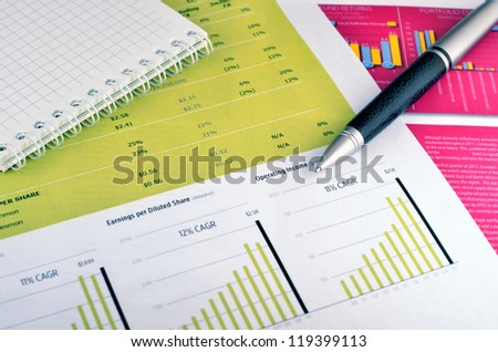 Diary and pen over annual report - stock photo