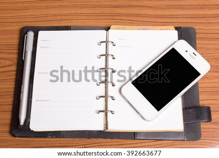 Diary note with smart phone on wood background (Organizer ,agenda, book, diary),the screen of phone can change with clipping path - stock photo