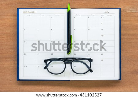 Diary planner book open calendar page june month with glasses and pen on the wooden desk - stock photo