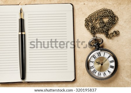 Diary with fountain pen and vintage pocket watch - stock photo