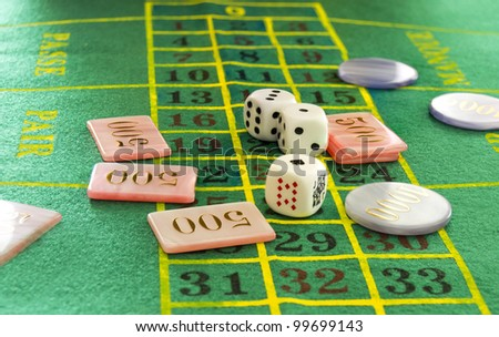 Dice and coins on green table - stock photo