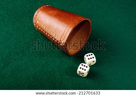 dice and leather cup on green cloth  - stock photo