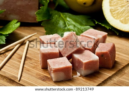 dice of mortadella with lemon on a chopping board - stock photo