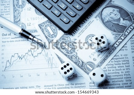 dice on financial chart near dollars and calculator on white table - stock photo