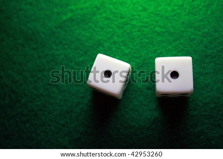 Dice over a green table showing snake eyes - stock photo