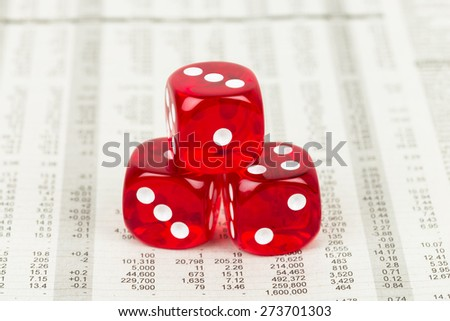 Dice stack rest on stock price detail financial newspaper - stock photo