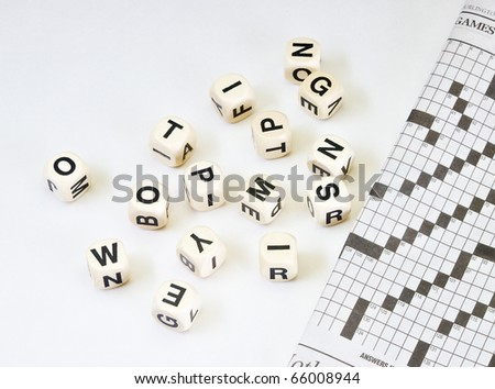 Dice with letters newspaper with crossword on old vintage distressed tabletop with copy space - stock photo