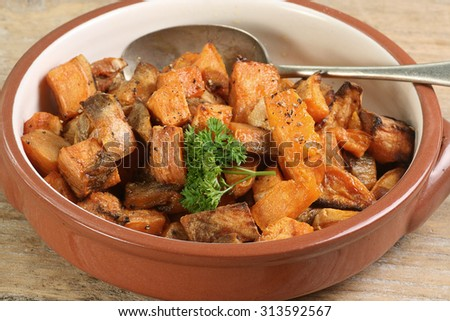 diced and roasted sweet potato with parsley garnish - stock photo
