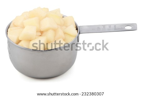 Diced pear flesh in an American cup measure, isolated on a white background - stock photo