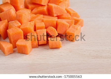 Diced raw carrots on a chopping board - stock photo