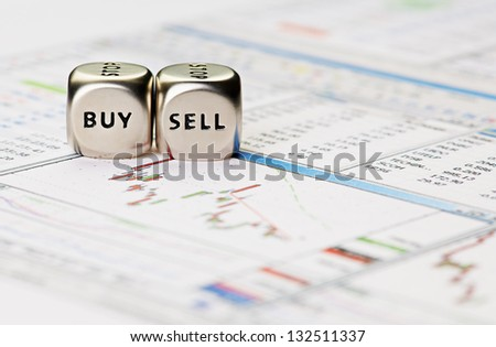Dices cubes with the words SELL BUY on financial downtrend chart graph. Selective focus - stock photo