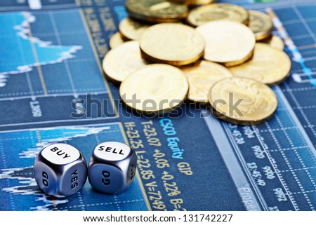 Dices cubes with words BUY SELL, coins and  financial chart as the background. Dices for traders. Selective focus - stock photo