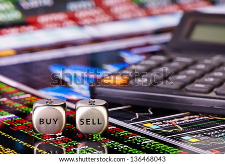 Dices cubes with words SELL BUY for trader and calculator. Financial chart and columns of figures as background. Selective focus - stock photo