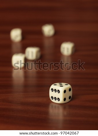Dices with selective focus on teak background - stock photo