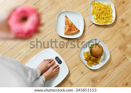 Diet And Fast Food Concept. Overweight Woman Standing On Weighing Scale Holding Donuts. French Fries, Hamburger And Pizza. Unhealthy Junk Food. Dieting, Lifestyle. Weight Loss. Obesity. Top View - stock photo