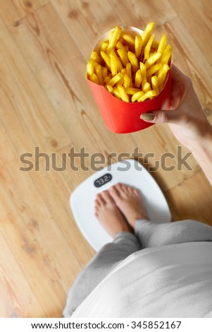 Diet And Fast Food Concept. Overweight Woman Standing On Weighing Scale Holding French Fries ( Fried Potato Chips ). Unhealthy Junk Food. Dieting, Lifestyle. Weight Loss. Obesity. Top View - stock photo