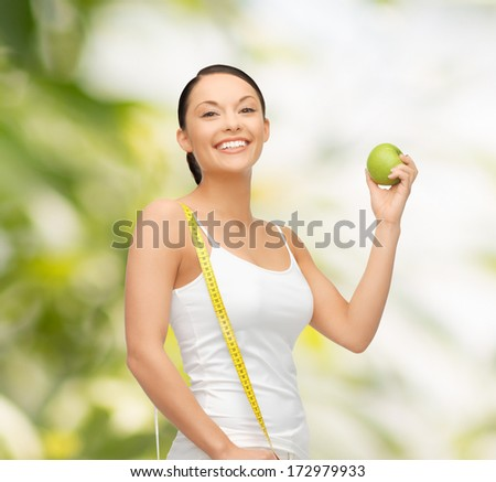 diet and health concept - beautiful sporty woman with apple and measuring tape - stock photo