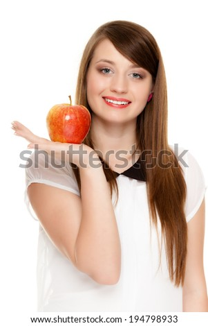 Diet and nutrition. Happy young woman offering apple seasonal fruit isolated on white. Girl recommending healthy lifestyle. - stock photo