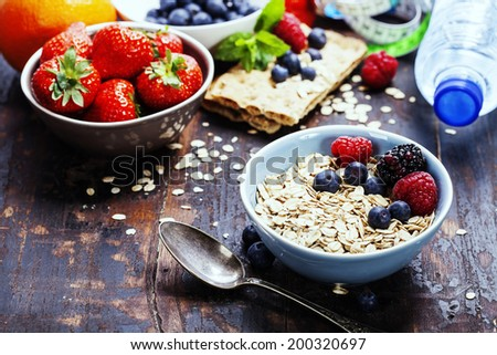 diet breakfast - bowls of oat flake, berries and fresh milk on wooden background - health and diet concept  - stock photo
