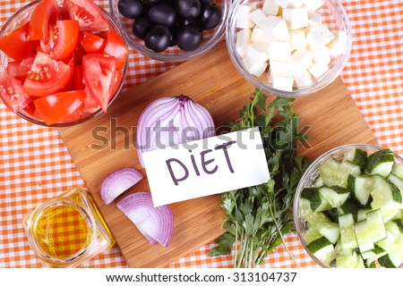 Diet concept, diet food. Kitchen table with food, cutting board. Vegetables on the table. Olives, red onion, feta cheese, tomatoes and herbs on the table. Greek salad ingredients. - stock photo