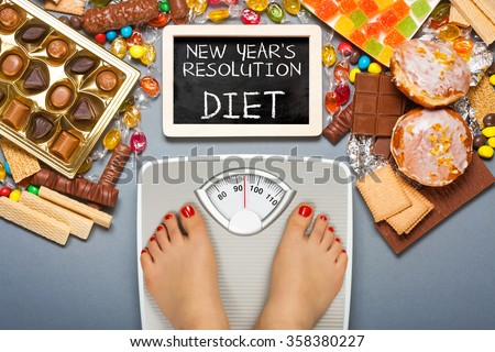 Diet concept. Feet of a young woman on bathroom scale and chocolate, jelly cubes, candies, chocolate bars, cookies, donuts, potato chips. Top view - stock photo