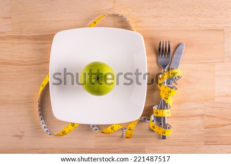 Diet concept. Green apple, Knife and fork wrapped in tape measure on plate. Above view - stock photo