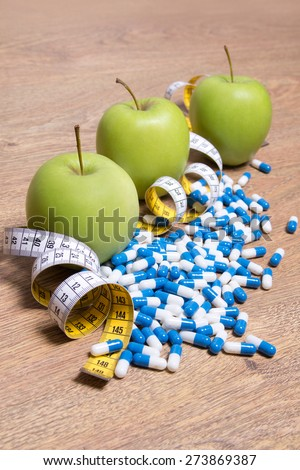 diet concept - green apples, pills and measure tape on wooden table - stock photo