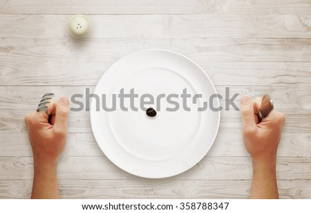 Diet concept of breakfast. Olive in an empty plate with hands on table. - stock photo