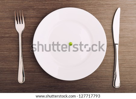 diet concept. one pea on an empty white plate with knife and fork - stock photo