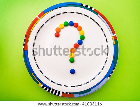 Diet concept (question mark made of candy on an empty plate) - stock photo