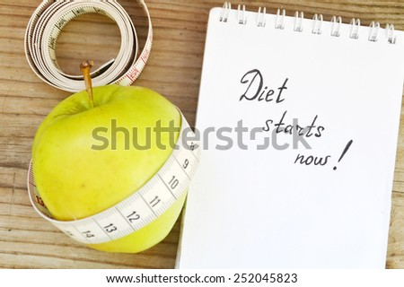 Diet concept with green apple, a notebook and a measuring tape on wooden table - stock photo