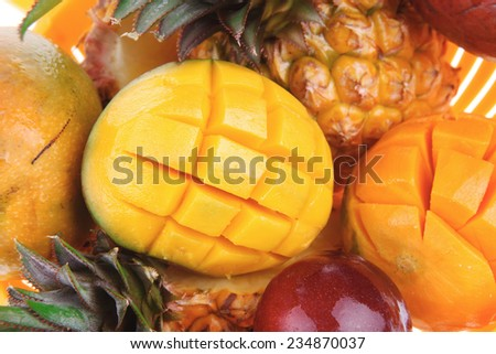 diet food - set of lot of tropical fruits include pineapple plum and mango in orange colander isolated over white background - stock photo