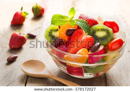 Diet-Fresh tasty mix fruit salad in the bowl on the wooden table, healthy breakfast, weight loss concept - stock photo