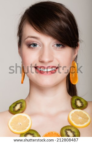 Diet. Girl with necklace and earrings of fresh citrus fruits on gray. Woman recommending healthy food and nutrition. - stock photo