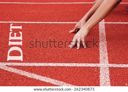 Diet - hands on starting line - stock photo