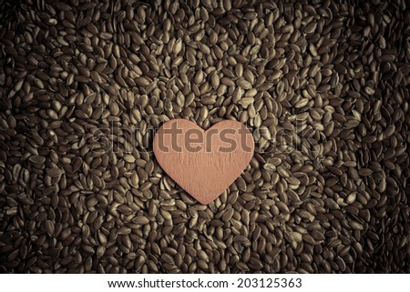 diet healthcare concept. Brown raw flax seeds linseed as natural background and red heart symbol. Healthy food  for preventing heart diseases. Flaxseeds are full of omega-3 fatty acids. - stock photo