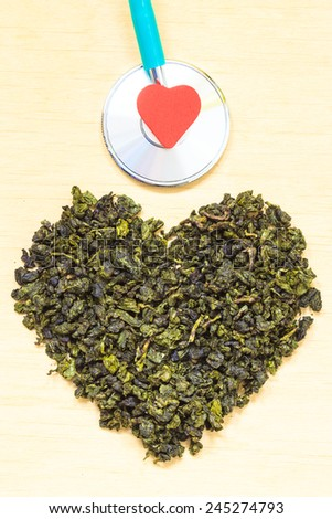 Diet healthcare concept. Green tea heart shaped stethoscope on wooden surface. Healthy food drink for lower heart disease risk - stock photo