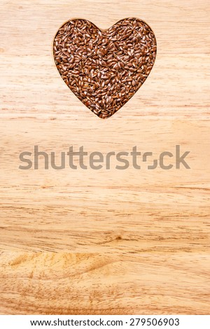 Diet healthcare healthy food. Raw flax seeds linseed heart shaped on wooden board background. - stock photo