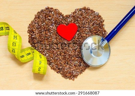 Diet healthcare weight reduction concept. Flax seeds linseed heart shaped stethoscope and measuring tape. Healthy food for preventing heart diseases, overweight. - stock photo