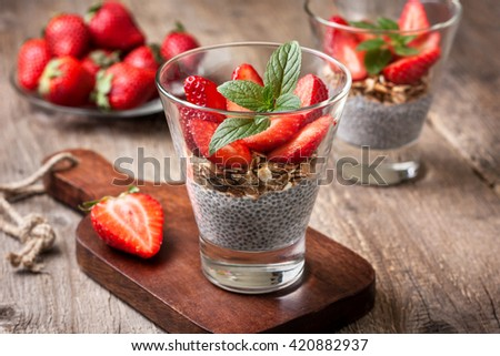 diet healthy breakfast. chia pudding, strawberries and muesli in a glass , fresh strawberry on  old wooden background - stock photo