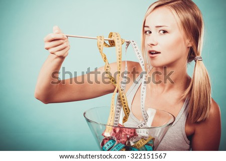 Diet, healthy food, weight loss and slim body concept. Fit fitness girl holding bowl eating colorful measuring tapes - stock photo