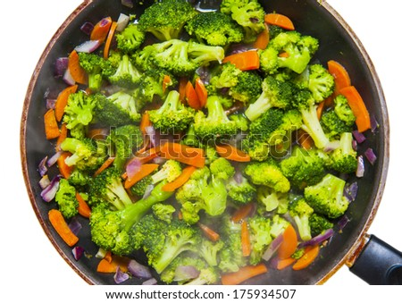 Diet lunch - stir fried vegetables in a pan (broccoli, carrot, red onion) - stock photo