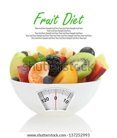 Diet meal. Fruit salad in a bowl with weight scale - stock photo