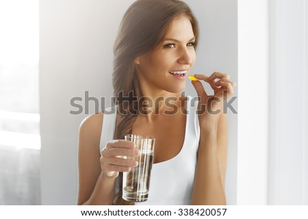 Diet. Nutrition. Healthy Eating, Lifestyle. Close Up Of Happy Smiling Woman Taking Pill With Cod Liver Oil Omega-3 And Holding A Glass Of Fresh Water In Morning. Vitamin D, E, A Fish Oil Capsules. - stock photo