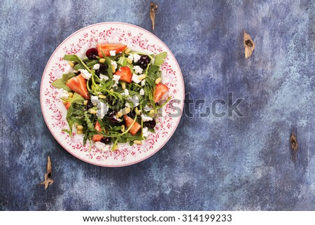 Diet or vegetarian concept. Fresh salad with arugula, cherry, strawberry, feta cheese on blue rustic background. Top view. Selective focus - stock photo
