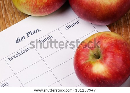 diet Plan. diet plan and a apples lying on a wooden surface - stock photo