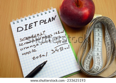 Diet plan. Measuring tape, a marker and a notepad with a daily diet plan - stock photo